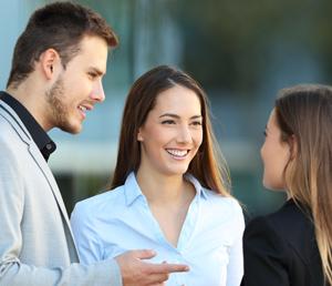 Mann spricht mit zwei Frauen und alle lächeln